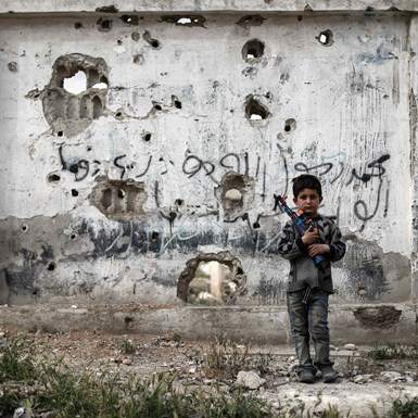 Syrian boy stands with a toy-gun
