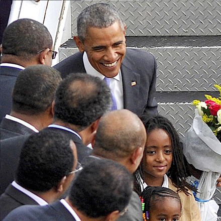 President Obama poses after receiving flowers from children while disembarking from Air Force One in Addis Ababa.