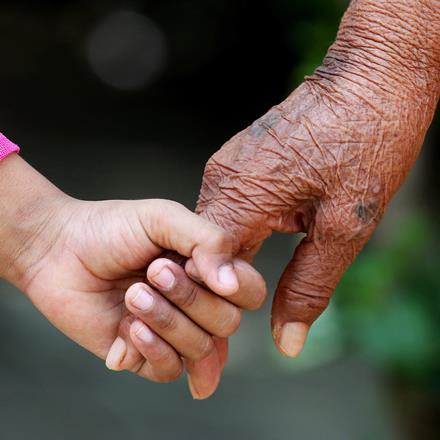 A young girl holds an elderly person's hand