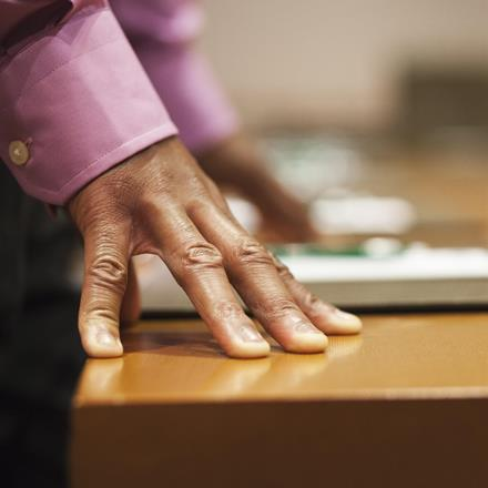 Man's hands on desk as he is standing, close up